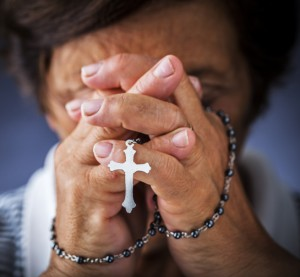 Old hands praying rosary, cropped lo res